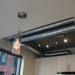 Exposed ductwork and pendant lighting in the kitchen