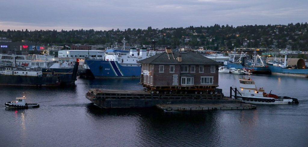 A large house is transported by boat near the Ballard Bridge in Seattle Wednesday, June 3, 2015.